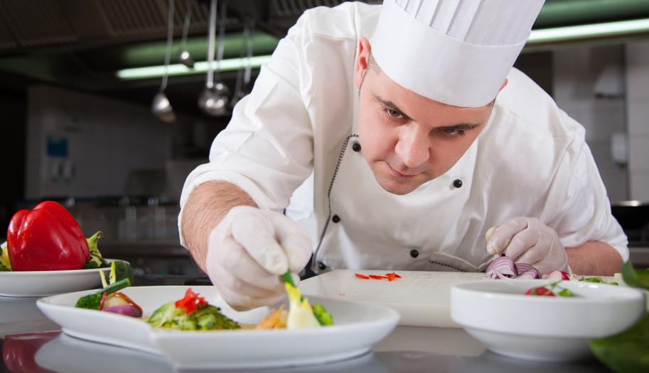 Chef preparando una comida con varios vegetales