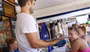 Generación de empleo en Hostelería y Turismo este verano. Camarero sirviendo mesas de turistas. elpaís.
